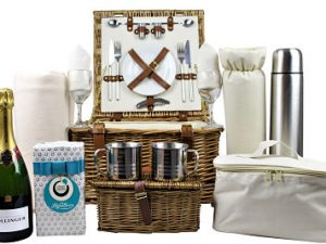 The Deluxe Fitted Picnic Basket with Champagne and Chocolates contains all you need for that perfect luxurious picnic treat. Willow picnic basket with cream insert and tan leather fastenings. Cups, plates, glasses, cutlery, flask, blanket along with a bottle of Bollinger champagne and luxury Lily O Brien's chocolates.